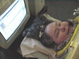 Η Dianne Odell με μικρόφωνο φωνητικής υπαγόρευσης στο κεφάλι της και την οθόνη του υπολογιστή πίσω από το κεφάλι της, την οποία βλέπει μέσω ενός καθρέφτη που έχει μπροστά της, προσαρμοσμένο πάνω στον κύλινδρο.